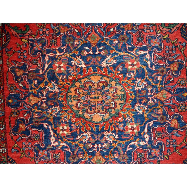 Vintage Persian Mashad rug in original condition. The field of the rug is in red shade with floral design on it. The...