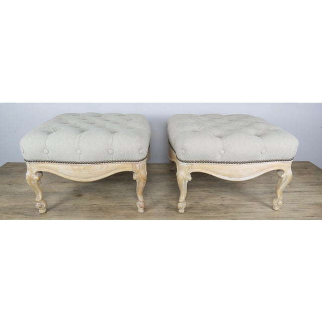 Pair of French Louis XV style natural wood benches newly upholstered in a neutral tufted linen textile and finished with...