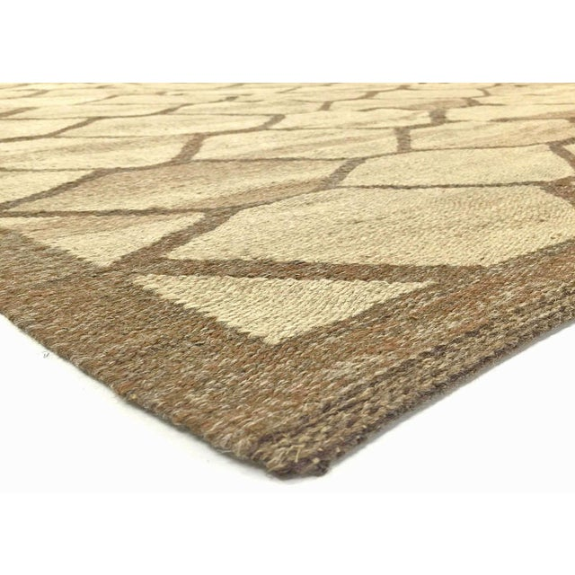 This is an Egyptian handwoven Kilim rug with an allover, geometric pattern inearth tones. Kilim rugs are a type of flat...