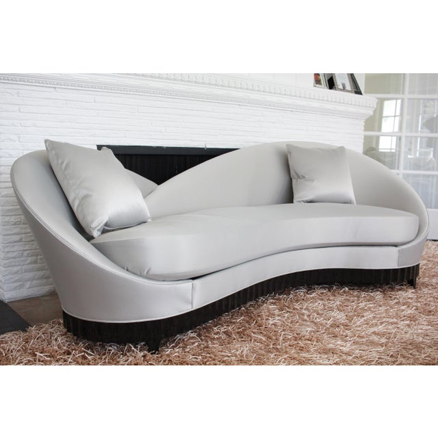 COURBÉ A sumptuous curved settee with sweeping asymmetrical lines, complimented by a beautifully carved scalloped apron....