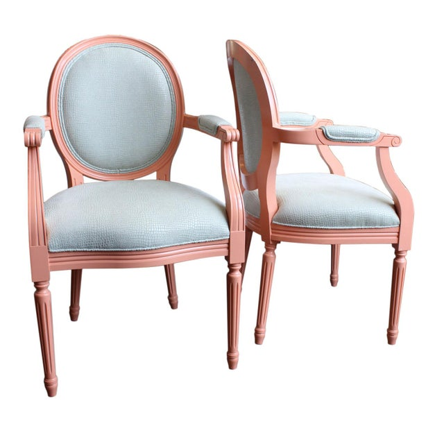 A pair of Louis XVI style arm chairs, re-upholstered in faux croc leather material, and painted in a peach cobbler color....