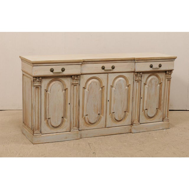 An American painted and carved wood buffet cabinet from the mid-20th century. This vintage American credenza,...