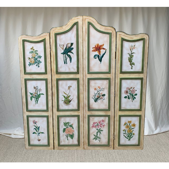 An enchanting vintage French hand-painted floral four panel wood screen features assorted botanical paintings framed by...