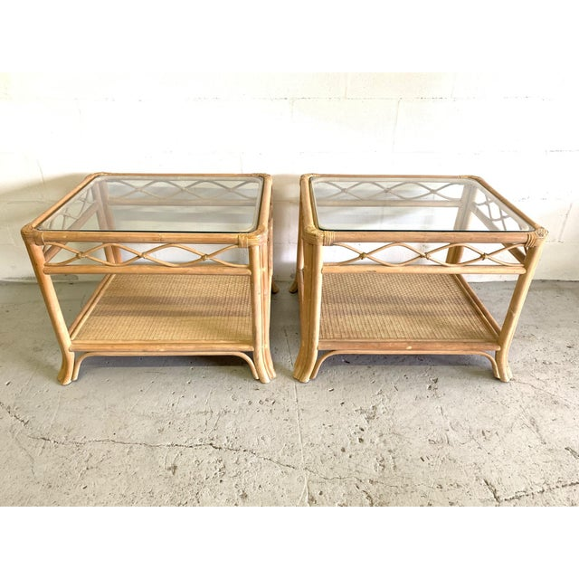 Pair of rattan end tables feature glass top woven wicker lower shelf. Perfect touch of island style to any decor. Good...