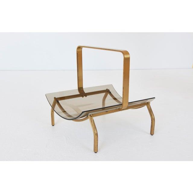 Fontana Arte magazine rack with smoked glass tray and brass stand.