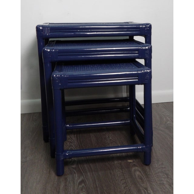 Set of three bamboo and wicker nesting tables in a new navy blue lacquer finish. This set of tables are in perfect...