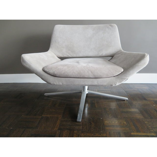 The seat that flows uninterruptedly into the armrests is the hallmark of this armchair. With aluminum swivel base and four...