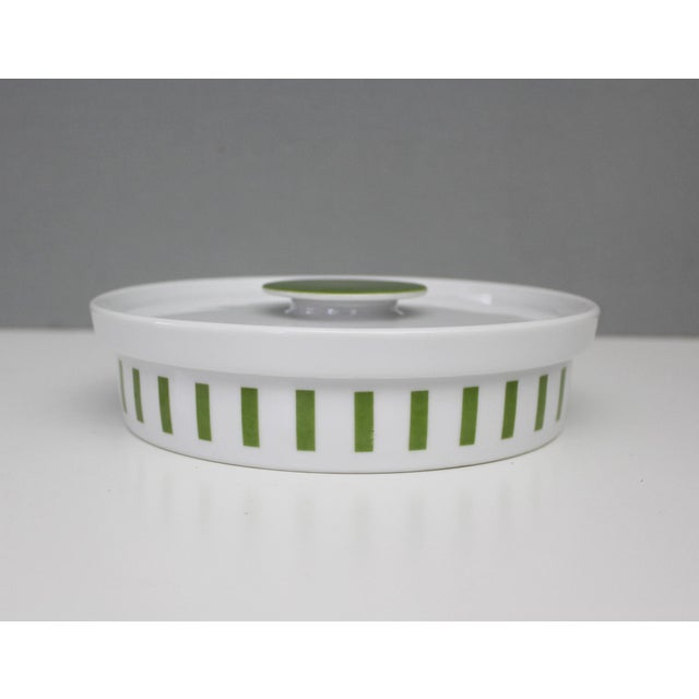 Small covered casserole dish by Lagardo Tackett for Schmid. White porcelain with green stripes and handle. Marked at...
