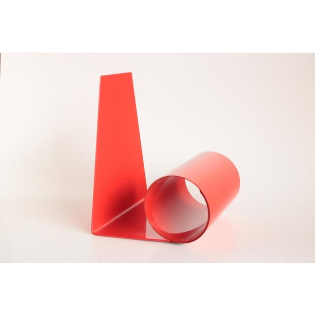 """Early 1970's coiled metal bookends with a tomato red enamel finish. Each piece unfurls to stylishly hold over 14"""" of books."""