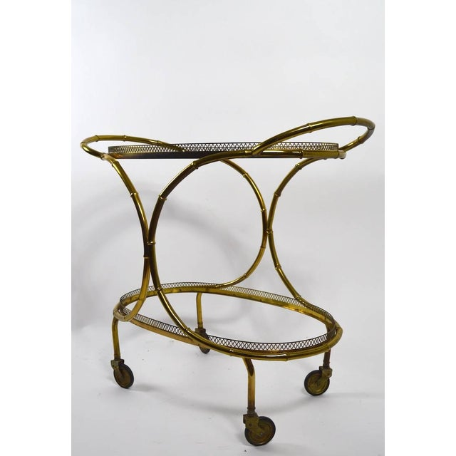Very chic and stylish serving cart, faux bamboo brass structure, with plate glass trays. Unusual and sexy form, very good...