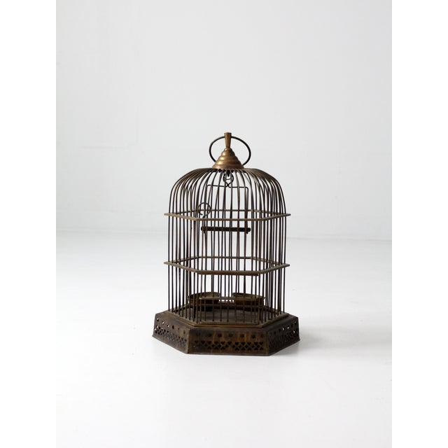 An antique solid brass bird cage. The decorative cage features cut-out stars and hearts around the base. Two brass feeding...