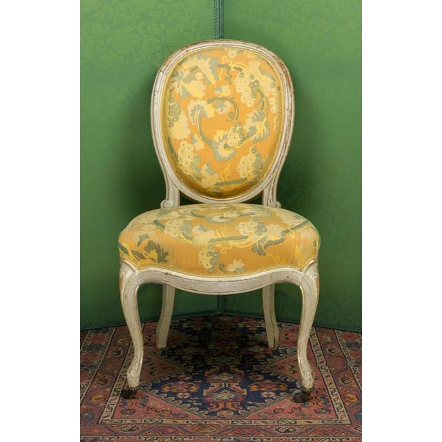 Pair of Louis XV style side chairs in a yellow patterned fabric with white painted frames with traces of gilt.