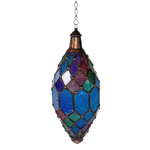 This Brilliant Imports hanging lantern in blue patterned glass with forrest green, deep red, and purple highlights and...