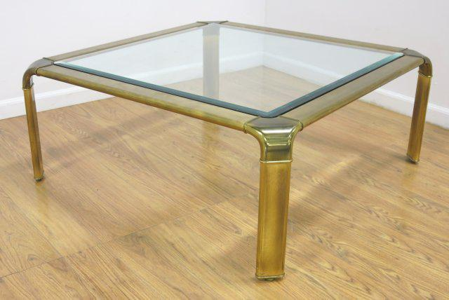 A Mid Century Modern Coffee Table With Brass Edging And A Glass Top. This