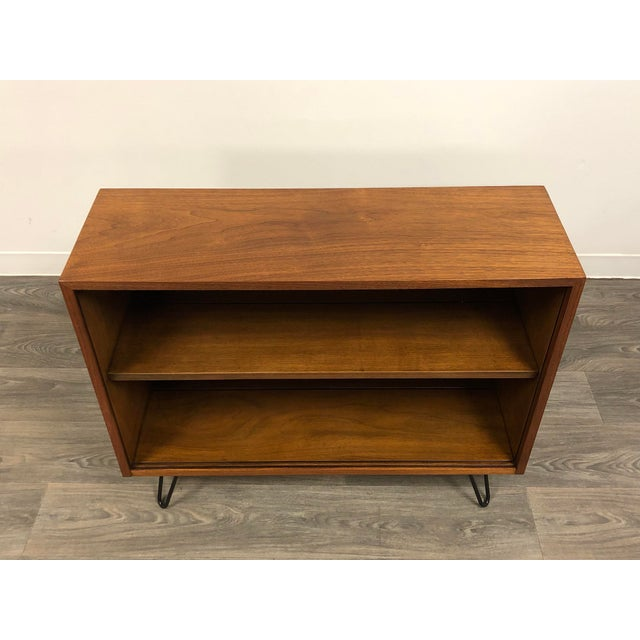 """A mid century modern walnut bookcase with black hairpin legs. Case made by American of Martinsville. 36"""" wide. 12"""" deep...."""