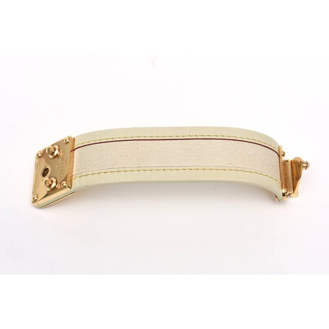 This iconic cuff bracelet by Louis Vuitton is beige stitched leather with beautiful gold plated brass hardware class and...