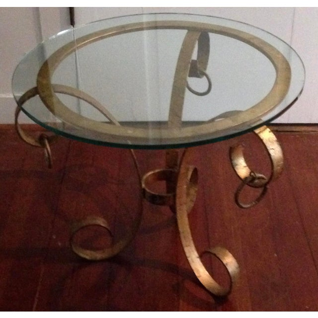 This Baroque 1970's scroll base and glass top table has distressed gilding. A beautiful, versatile Hollywood Regency...