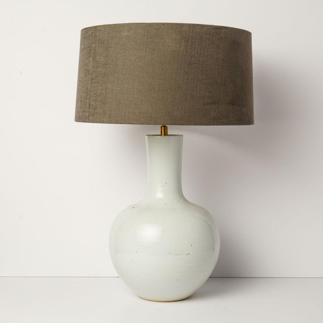 Custom white glazed table lamp with bulbous body and slender neck. Sold with complimentary dark gray linen shade. Listed...