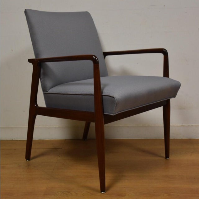 """A mid century modern walnut and blue-grey upholstered lounge chair by Stow Davis. Seat height is 19""""."""