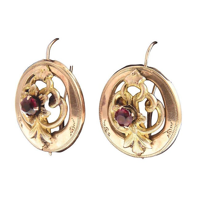 Victorian 14K gold earrings featuring oval etched frames with floral design in the center, each with a prong-set garnet....