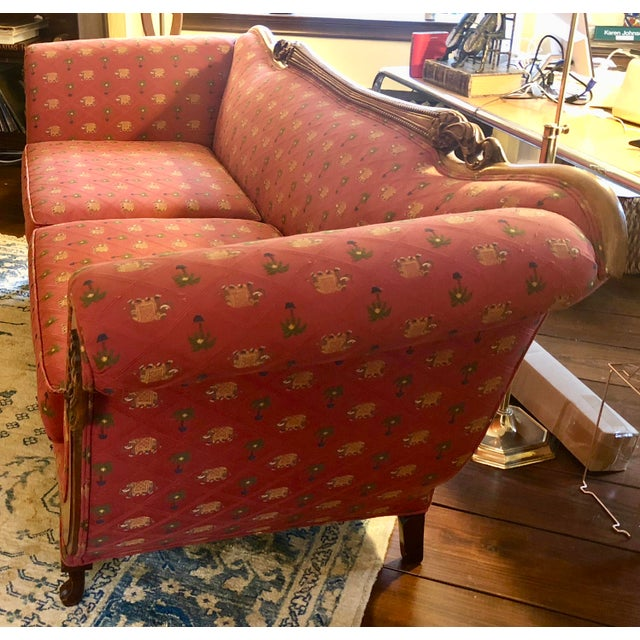 Early 20th Century Sofa with beautiful carved wood scrolling. Sofa has been reupholstered with quality red rust fabric...