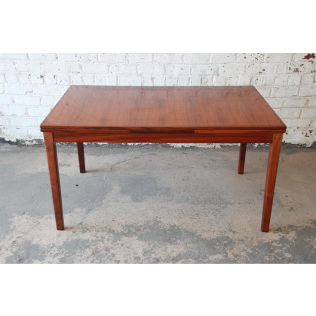 Offering an exceptional Danish Modern rosewood extension dining table designed by Arne Vodder for Sigh & Sons. The table...