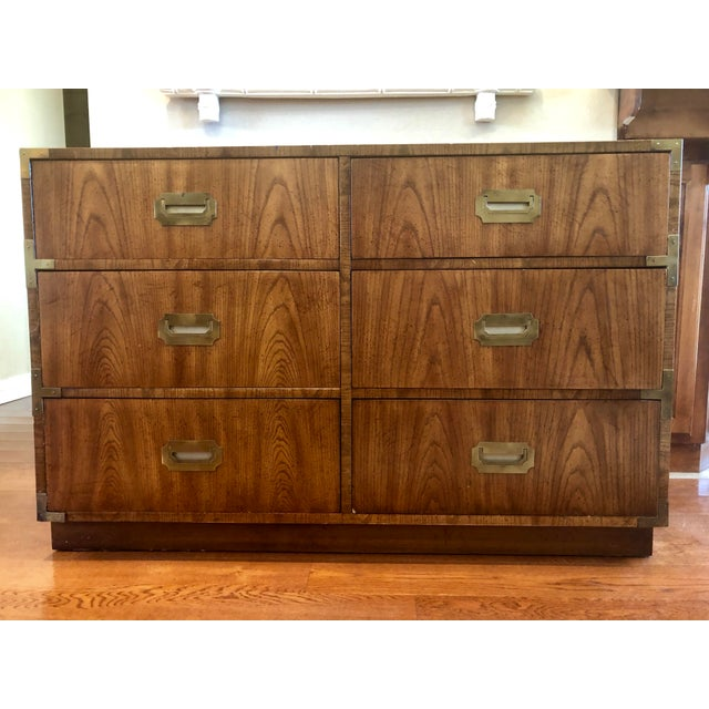 Six drawer Dixie Campaigner dresser. Solid construction with brass accents and campaign style brass drawer pulls. Vintage...