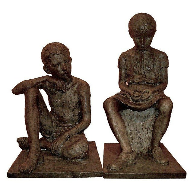 France, early 20th century. Pair of two lifesize sculptures, brother and sister, the boy sitting cross-legged and the girl...