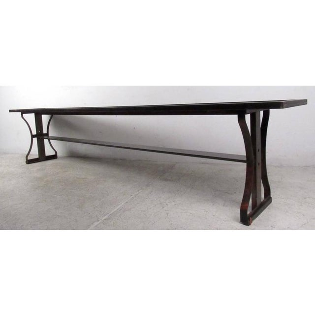 Stylish long industrial bench featuring sculpted iron body with unique form, very solid piece for occasional seating in...