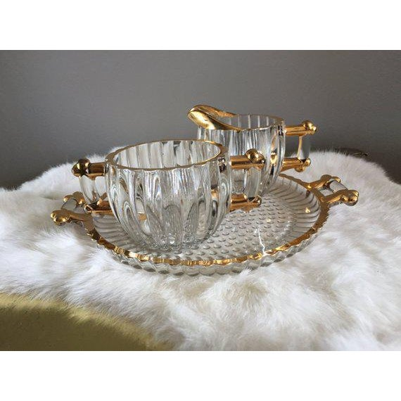 Beautiful cream + sugar bowl set that sits on matching glass tray with handles. Gorgeous gold accents and faux bamboo...