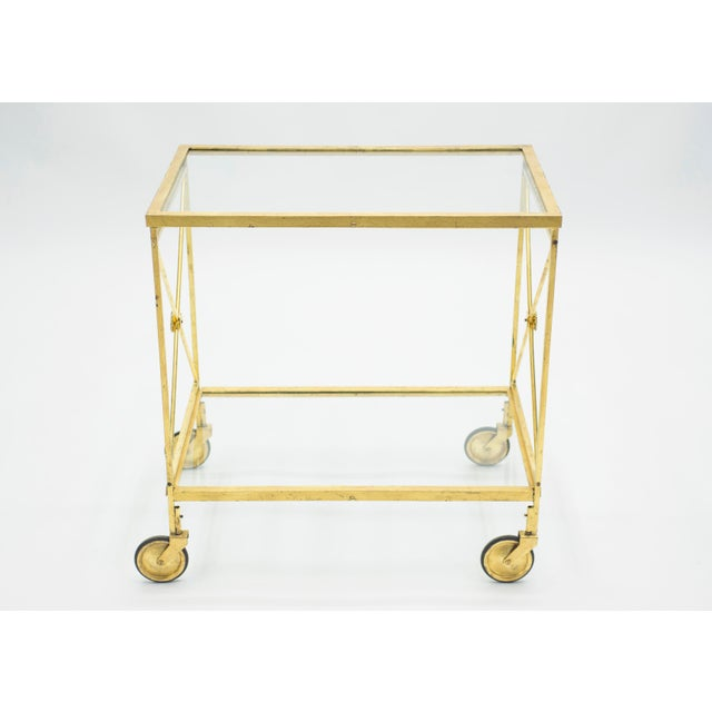 This chic bar cart from the 1960s carries with it the elegant mood of the neoclassical post art deco period. Glittering in...