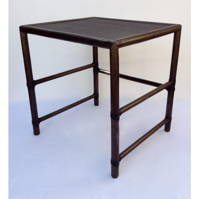 c1990s; McGuire rattan and cane topped, rectangular shaped, leather strapped side or end table. Table has a square mesh...