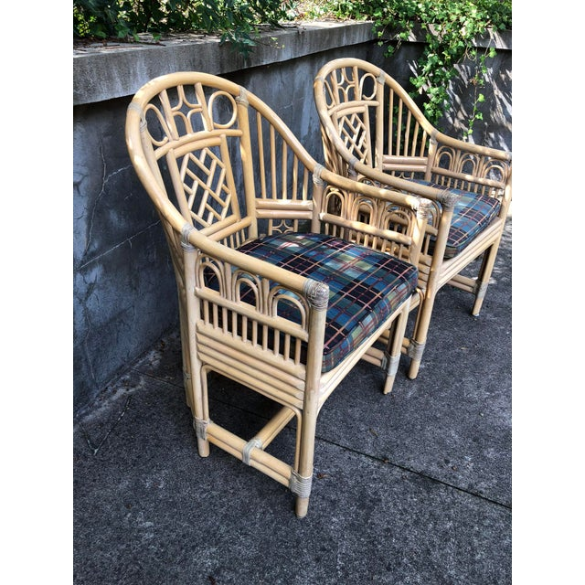 Pair of bamboo and rattan armchairs with caned seats and loose cushions in the Brighton Pavilion Chinoiserie style form....