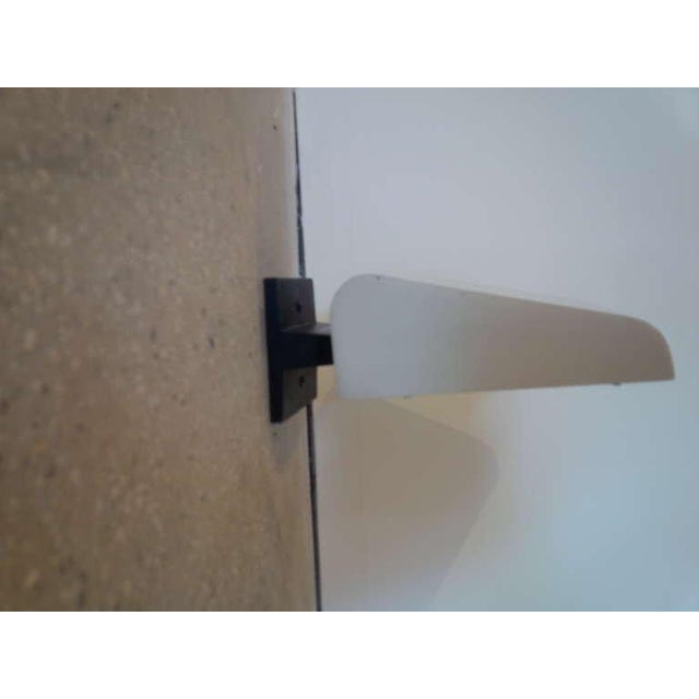 Pair of modernist outdoor / indoor sconces by Kurt Versen. USA, circa 1950. Signed. Bone white metal shade with black...