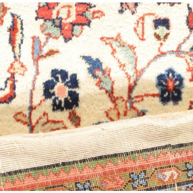Vintage handwoven Sarouk rug with a floral design on a ivory field.