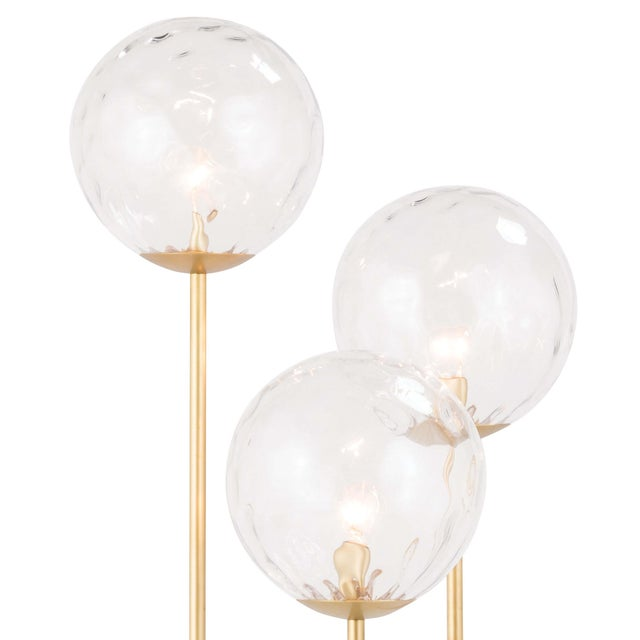 Stunning and elegant, the Rio Triple floor lamp features optical glass spherical shade accented by polished nickel...