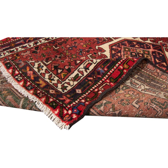 Beautiful Vintage Persian Heriz Handmade Wool Runner with a red field. This runner has multi-color accents in an allover...