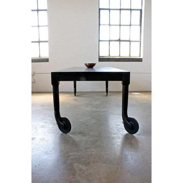 The Shaker-influenced rolling dining table features hand-carved, swivelling solid wood casters, with brass wheel locks....