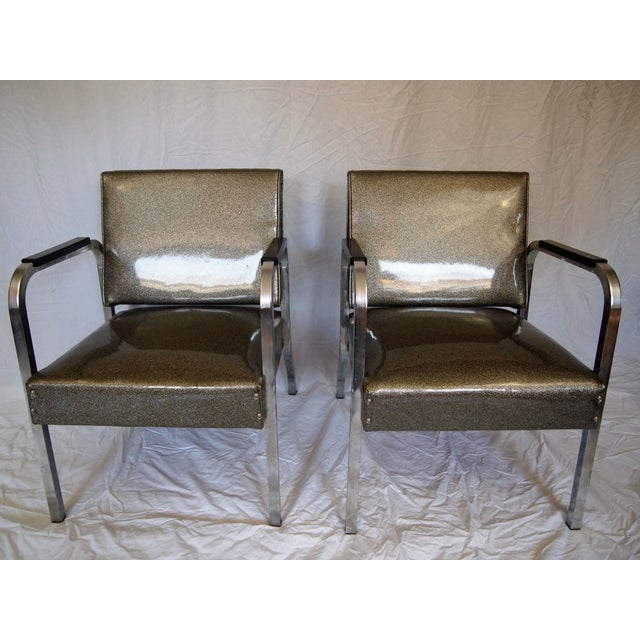 A pair of metal chrome chairs with silver vinyl upholstery. Each chair shows wear from age and minor rust. Seat height...
