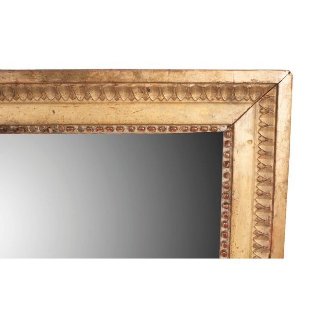 A Louis XVI gilt mirror with original mercury glass.