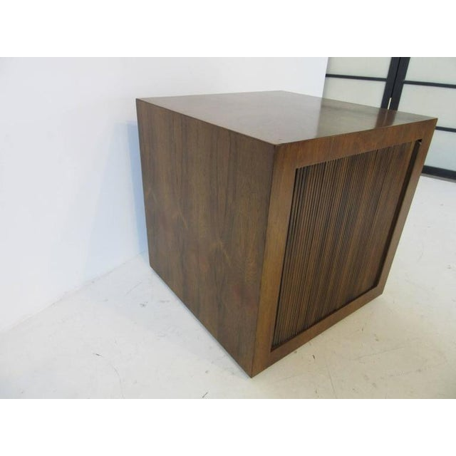 A rolling bar cube in a rich Brazilian rosewood with a tambour door reveling storage and a bottle shelve with cut away...
