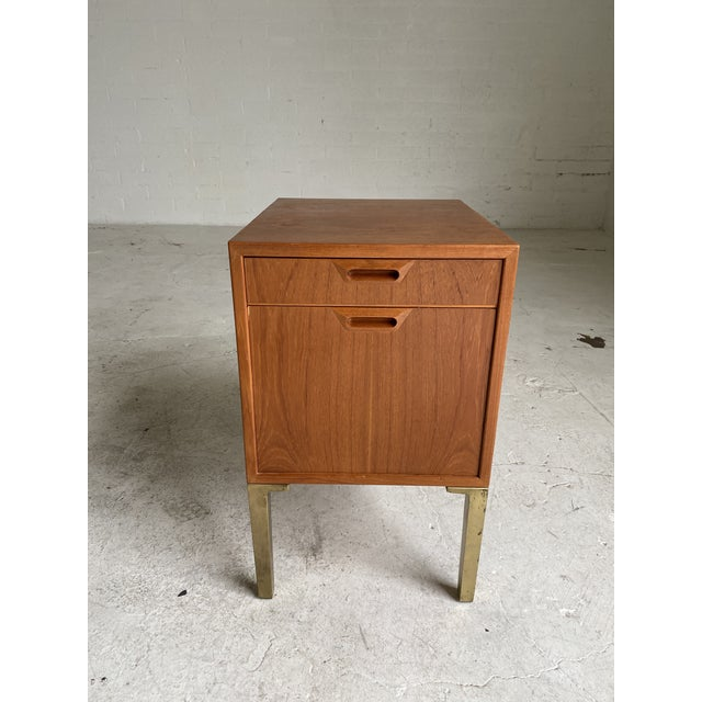 """Small teak filing cabinet with brass legs. In excellent condition. Dimensions: 16""""W x 19.5""""D x 26.25""""H"""