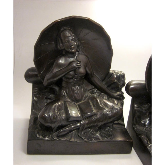 This is a stunning pair of cast metal Art Nouveau or Art Deco bookends. Each features a seated female figure, nude from...