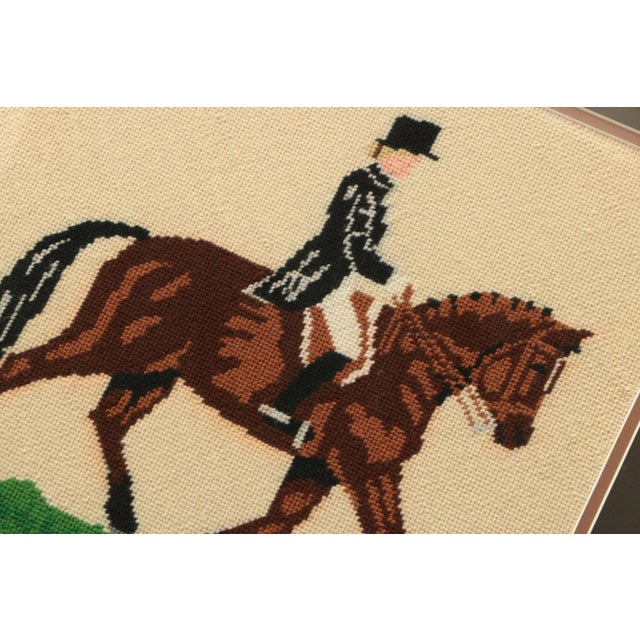 Vintage needlepoint, stitched by an expert hand in wool and custom framed in a dark wooden frame. This horse and its rider...