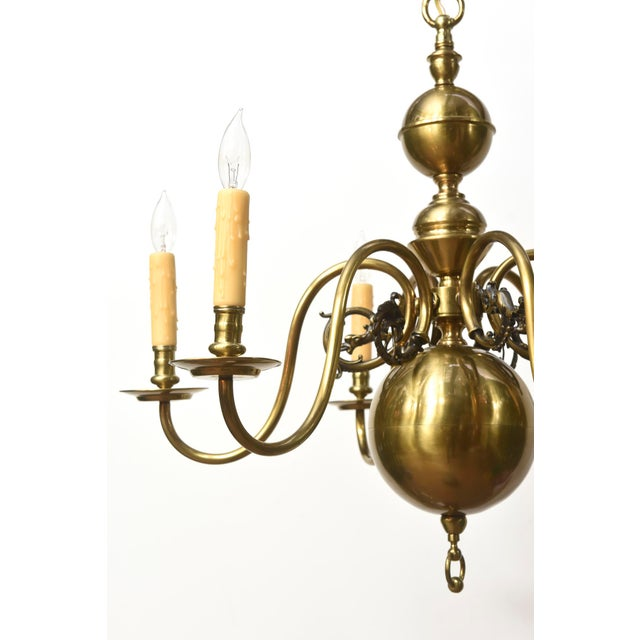 Colonial chandelier with cast gryphon details on the arms. Completely restored and rewired with an antique brass patina....