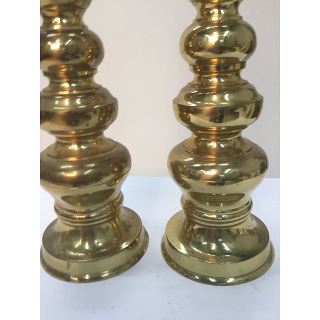 Impressive tall solid brass candleholders . Original labels on bottom . Some patina