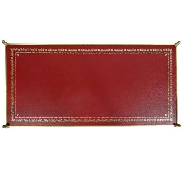 Rectangular to with inset tooled red leather top, with pineapple finials raised on circular legs with an X-form stretcher...