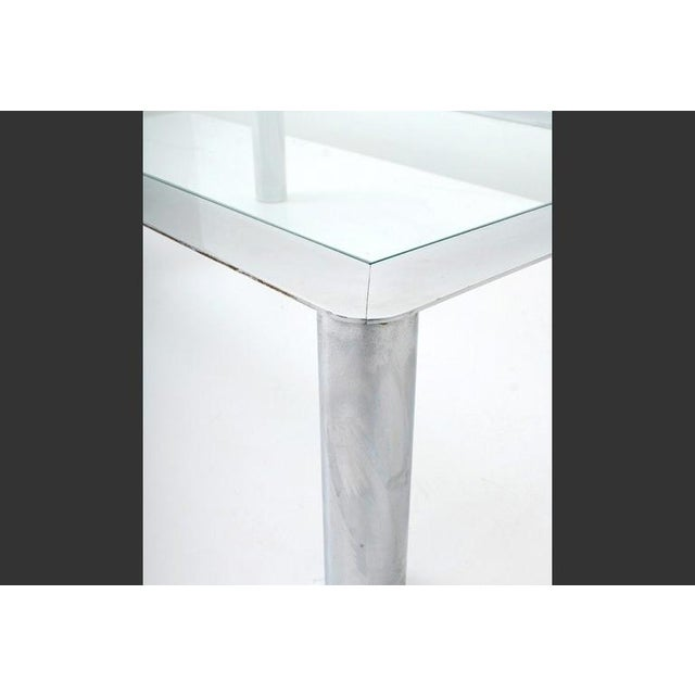 A steel low table with cylindrical legs and a thin chrome apron with inset glass. Designed for Cinova, a leading...