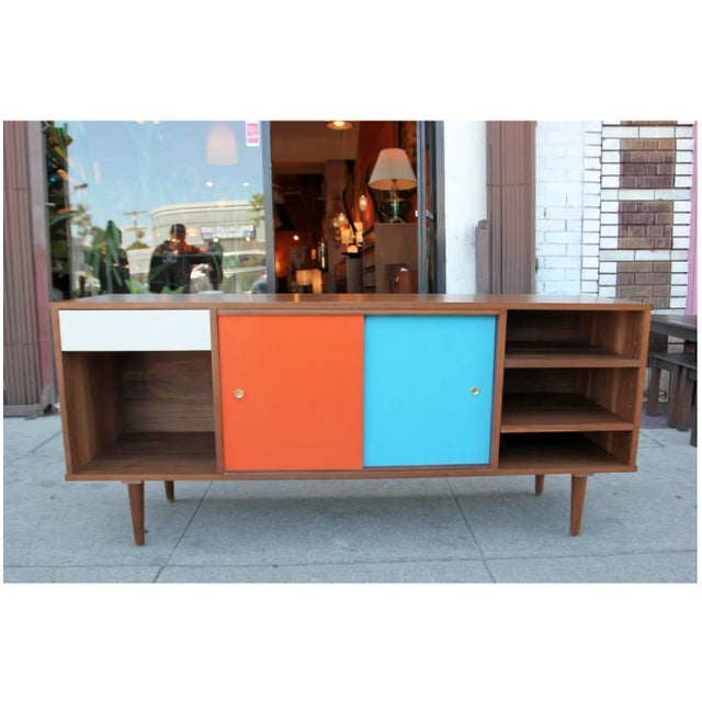Walnut credenza hand made in the United States. The credenza features a working drawer on the left side, and on the center...