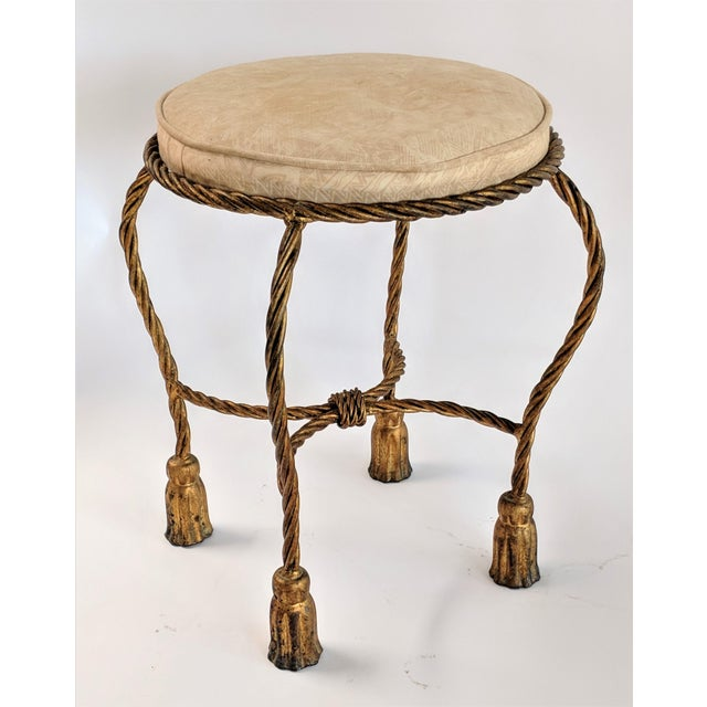 Gilt metal vanity stool with rope and tassel motif. Circa 1960. I need of reupholstery.